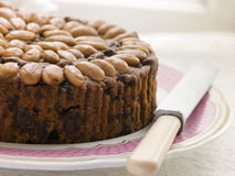 Dundee Cake on a Plate. With nuts and a cutting knife on the red plate Stock Photography