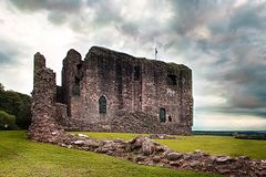 Dundonald Castle Ruins on a cloudy day with green grass. Dundonald Castle on a cloudy day with scottish flag flying on top. Viewed from the front deteriorated royalty free stock photos