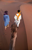 On the dune. Camel driver and tourist guide walk on the top of dune with tourist caravan. Merzouga, Marocco Stock Photos