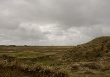 Dune area on Romo island, Denmark. Showing grass covered sand hills under a cloudy sky stock photography