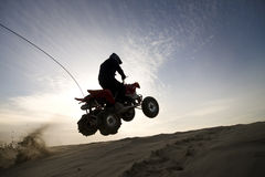 Dune atv jump in the sunset. Silhouette of an ATV rider jumping in the sunset Stock Photography