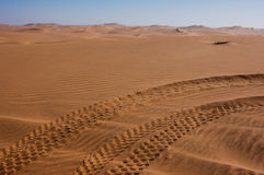 Dune Buggy Tracks in the Kalahari Desert. Paired sets of dune buggy tracks in the Kalahari Desert crossing the photo from lower left to upper right; scalloped Royalty Free Stock Photo