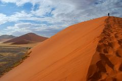 Dune 45 climbing. Sossusvlei, Namibia. Dune 45 is a star dune in the Sossusvlei area of the Namib Desert in Namibia. Its name comes from the fact that it is at Stock Image