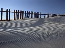 Dune de sable contre des barrières Photographie stock