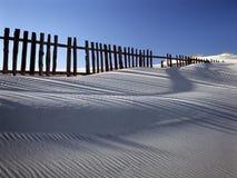 Dune de sable contre des barrières photographie stock libre de droits