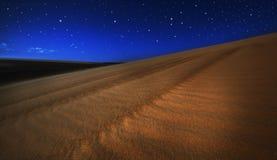 Dune di sabbia sotto l'indicatore luminoso e le stelle di luna piena Fotografia Stock Libera da Diritti