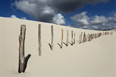 Dune with fence. White dune with a fence and cloudy sky stock photos