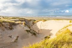 Dune landscape Dutch coast with sand drifts and wind eroded deep holes. Dunes on the Dutch North Sea coast at IJmuiderslag with wind sweeping stripes in the sand Stock Image
