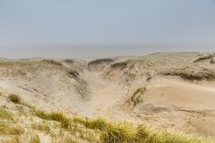 Dune landscape Dutch coast with sand drifts and wind eroded deep holes. Dune landscape in the winter at Dutch coast with by autumn storms deep carved out  wind Royalty Free Stock Photography