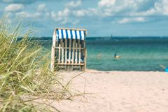 Dune with some grass and traditional wooden beach chairs on the sandy beach. Northern Germany, on the coast of Baltic Stock Image