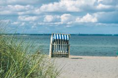 Dune with some grass and traditional wooden beach chairs on the sandy beach. Northern Germany, on the coast of Baltic. Sea Stock Photography