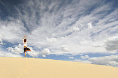 Dune Yoga. A woman in the Tree pose on a sand dune in Death Valley National Park, California Stock Photo