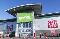 Dunelm与销售海报和蓝天背景的商店前面 图库摄影