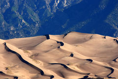 Sand Dunes. Close-up of ridge formation in sand dunes against blue mountains in background Royalty Free Stock Photo