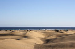Dunes with atlantic ocean. On horizon with blue sky. Gran Canaria Royalty Free Stock Photos