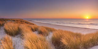 Dunes and beach at sunset on Texel island, The Netherlands. Tall dunes with dune grass and a wide beach below. Photographed at sunset on the island of Texel in Stock Image