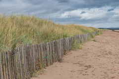 Dunes behind a fence Royalty Free Stock Image