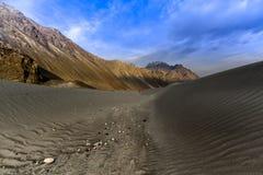 Dunes de sable dans la perspective de gamme de montagne et de ciel colorés éloignés de lever de soleil Images stock