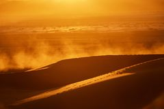 dunes, dust, and backlight at dusk in the desert stock photos