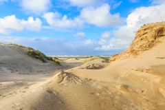 Dunes on Dutch North Sea coast at IJmuiderslag with wind sweeping stripes in the sand. Against the background of blue sky with scattered clouds Royalty Free Stock Images