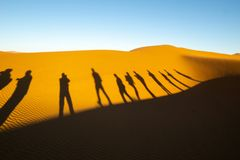 Dunes of Hidden Vlei, Sossusvlie Namibia. Row of tourists shadows on dunes of Hidden Vlei, Sossusvlie Namibia Royalty Free Stock Image