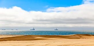Dunes of Kalahari desert and Atlantic ocean shore, with oil rigs royalty free stock photo
