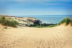 Dunes in Lithuania. Landscape of golden color dunes with green grasses, beautiful sky and the sea at Neringa, Naglis reserve near Pervalka in Lithuania stock photo