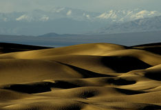 Dunes and Mountains. Dunes of Death Valley, CA with snowy mountain range in the distance Stock Images