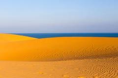 Dunes onduleuses arénacées jaunes avec la mer bleue au fond Photographie stock