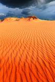 Dunes in sand desert under dark sky before thunder storm Stock Images