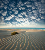 Dunes of sandy beach on background of sea and sky clouds Royalty Free Stock Image