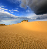 Dunes in sandy desert under thunder sky Stock Images
