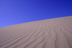 Dunes Series. Sand dune with ripples and blue sky Stock Images