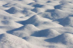 Dunes of snow in a country field Royalty Free Stock Photo