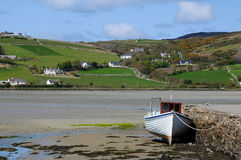Dunfanaghy harbor in Donegal Ireland horizontal. A fishing boat lies aground at the quay at low tide in Dunfanaghy, Donegal, Republic of Ireland.  Farmland is Stock Photography