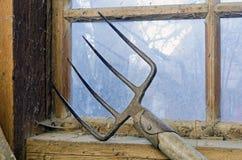 Dung-fork at a dirty cobwebbed window Stock Photos