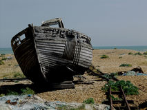 Dungeness beach with boats, Kent. Dungeness beach, kent, showing wrecked boats and buildings Royalty Free Stock Images