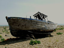 Dungeness beach with boats, Kent. Dungeness beach, kent, showing wrecked boats and buildings Royalty Free Stock Photo