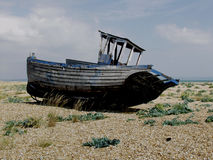 Dungeness beach with boats, Kent. Dungeness beach, kent, showing wrecked boats and buildings Stock Photos
