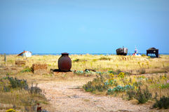Dungeness beach view Kent United Kingdom. Old fishing boats in the yellow grass of Lydd-on-Sea sandy beach and Dungeness Nature Reserve looking north to Royalty Free Stock Image