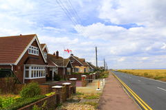 Dungeness coastal road Lydd-on-Sea United Kingdom. Dungeness coastal road and roadside houses of Lydd-on-Sea village.Lydd-on-Sea is a modern village, mostly Stock Images