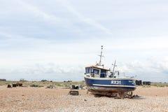 DUNGENESS, ENGLAND - CIRCA im Juni 2014 - Weinleseszene mit dem alten getragenen Boot an Land gesehen Lizenzfreies Stockfoto