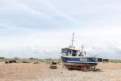 DUNGENESS,ENGLAND - CIRCA JUNE 2014 - Vintage scene with old worn boat seen ashore Royalty Free Stock Photo
