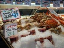 Dungeness-Krabbe und Krabbencocktails, die in der Eisspeicherfront an einem Meeresfrüchte fishermans Markt sitzen stockbilder