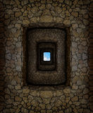 Dungeon with stone walls and light window high above. Dungeon with stone walls and hard-to-reach hole with blue sky high above stock images