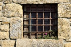 Dungeon window. With blooming flowers Royalty Free Stock Photos