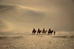 DUNHUANG, CHINA 11 DE MARÇO: O grupo de turistas está montando camelos dentro Imagens de Stock