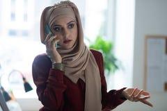 Dunkeläugiges Frauengefühl emotional beim Sprechen am Telefon lizenzfreies stockfoto