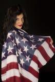 Dunkel - complected Frau mit der amerikanischen Flagge drapiert über Schulter Lizenzfreies Stockfoto