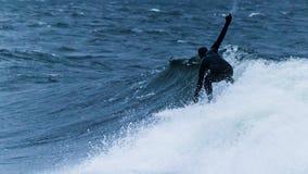 Dunkel-entsprochener Surfer in der Aktion lizenzfreie stockfotos